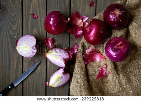 red spanish onions on rustic wooden table, selective focus - stock photo