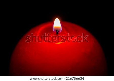 Red sphere candle and flame in dark night