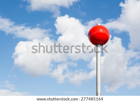 Red sphere on a steel leg resembles a huge lollipop - stock photo