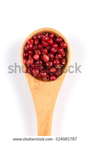 red spice pepper peppercorns in a spoon over white