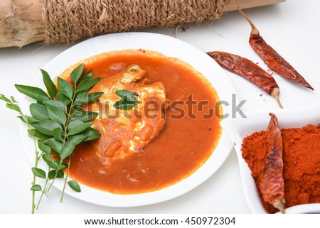 Red spicy hot Kerala fish curry and green curry leaf, India. South Indian sea food with pearl spot/ tilapia. Popular in coastal area of Sri Lanka. with green chili, coconut milk, mango Asian cuisine. - stock photo