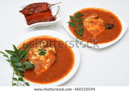 Red spicy hot Kerala fish curry and green curry leaf, India. South Indian sea food with pearl spot/ tilapia. Popular in coastal area of Sri Lanka. with green chili, coconut milk, mango Asian cuisine.