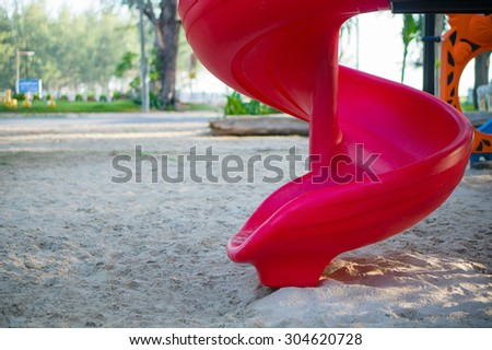 Red spiral slide form crawl construction on modern kids playground - stock photo