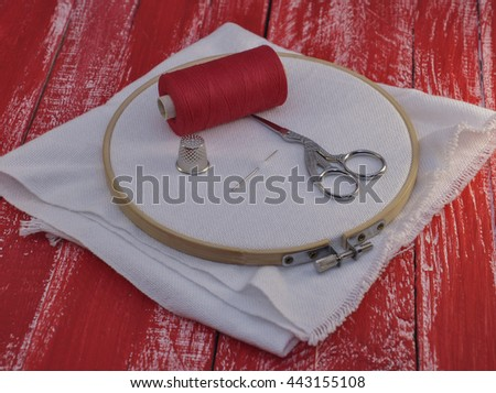 Red spool of thread and fabric in the wooden embroidery hoop for embroidery and needlework - stock photo