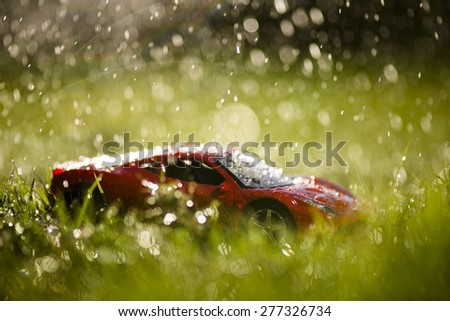 Red sport car under the rain in the meadow. - stock photo