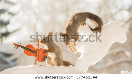 red squirrels in snow with ice squirrel saxophone and violin  - stock photo