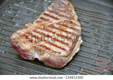 Red Steak in a frying pan - stock photo