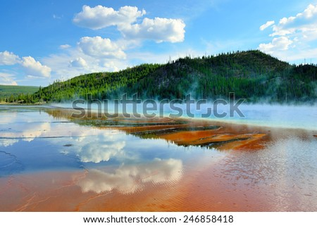 red steamy surface and reflection of the clouds in Midway Geyser Basin in Yellowstone National Park, Wyoming - stock photo