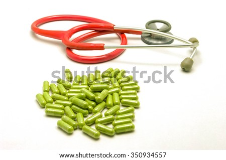 Red stethoscope and  capsule on a white background