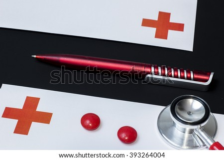 red stethoscope next to the envelope on a black background