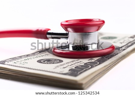 Red stethoscope on a pile of dollars closeup isolated on white background