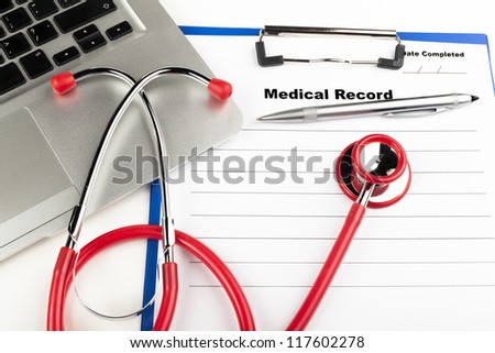 Red stethoscope on  blue clipboard  with medical record close-up with silver colored laptop - stock photo