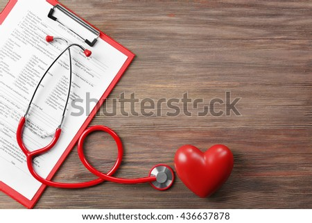 Red stethoscope with prescription on wooden background - stock photo