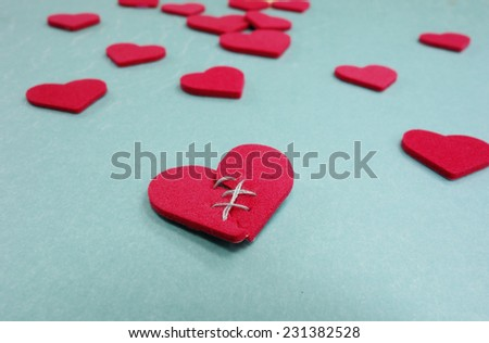 Red stitched broken heart and assorted hearts on blue                                - stock photo
