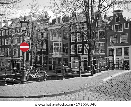 red stop on black and white cityscape of Amsterdam - stock photo