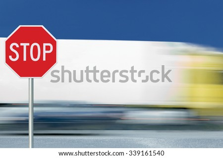 Red stop road sign, motion blurred truck vehicle traffic in background, regulatory warning signage octagon, white octagonal frame, metallic pole post - stock photo