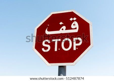 Red stop sign in English and Arabic