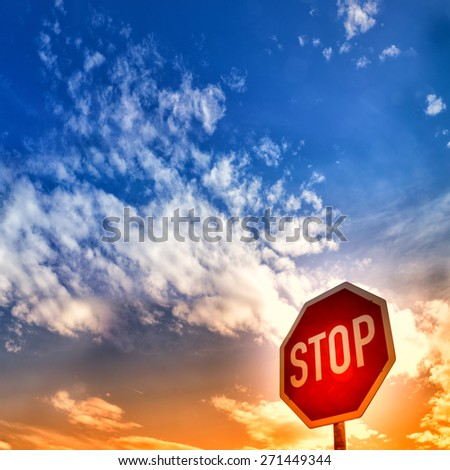 red stop sign with blue sky and clouds - stock photo