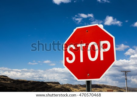 Red stop sign with mountain and sky background as the symbolic of warning,caution of safety drive,summer road trip,travel and go back home happily