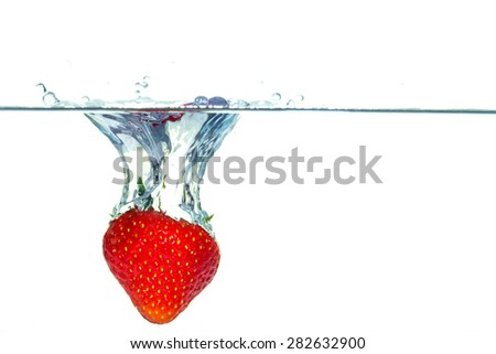 Red strawberry falling into water with a splash - stock photo