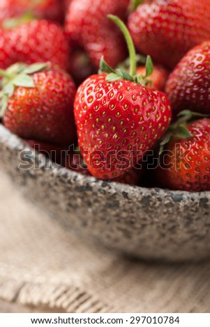 Red strawberry in a bowl on wooden table close-up