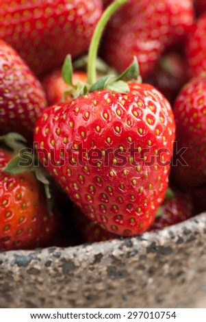 Red strawberry in ceramic bowl close-up