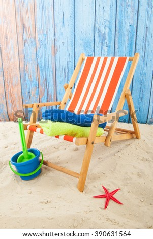 Red striped beach chair and toys in sand  - stock photo