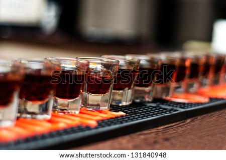 Red, strong alcoholic drink in small glasses on bar waiting to be served - stock photo
