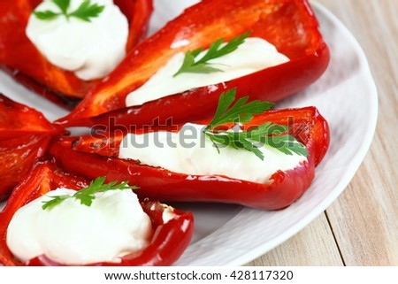 Red stuffed grilled pepper filled with cream cheese on the plate.