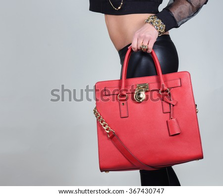 Red stylish glamorous female leather bag on pure background. Fashionable and high style expensive female bag. Sales bag fashion concept