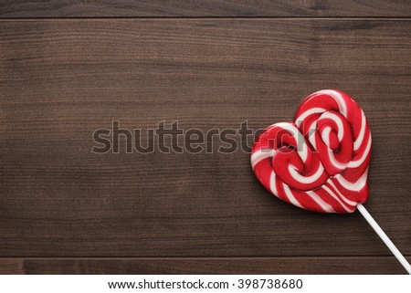red sugar lollipop on the wooden table - stock photo