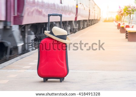 red suitcase at train station with sunset light, focus at suit case - stock photo