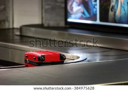 Red suitcase waiting be picked up on a conveyor belt