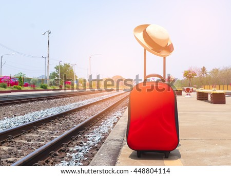 Red suitcase with a woman hat  at the train station with abstract light in retro effect - stock photo