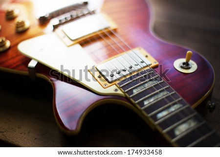 Red sunburst color single cutaway electric solid body guitar, on a old grungy wooden surface. Shallow depth of field. Dreamy feeling. - stock photo
