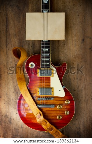 Red sunburst solid body electric guitar, with blank old paper on the neck for your message. - stock photo