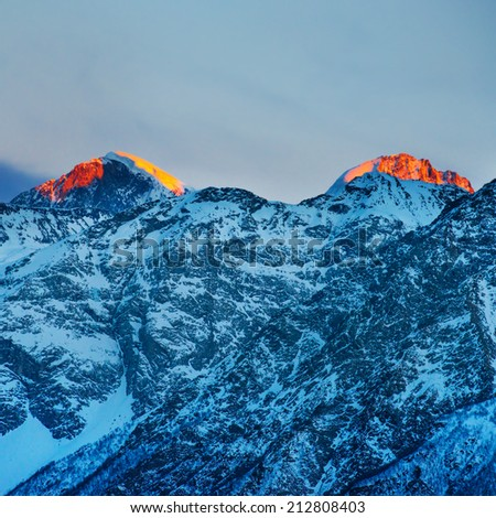 Red sunset in mountains covered by snow.