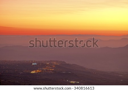 red sunset on the lavic plateau of Adrano and the layers of the mountain across the river Simeto, Sicily