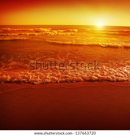 Red sunset on the sea shore. - stock photo