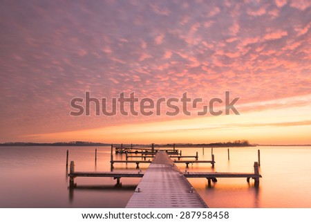 Red sunset over a lake with a jetty and golden bright light - stock photo