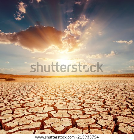 red sunset over cracked earth - stock photo