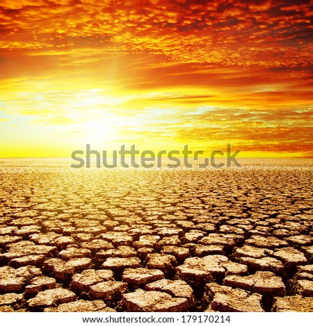 red sunset over drought earth - stock photo