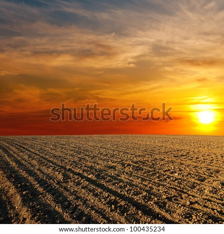 red sunset over ploughed farm field - stock photo