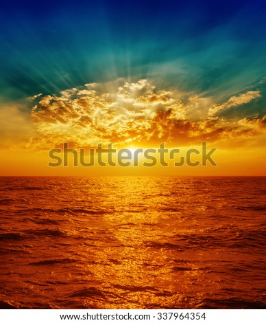 red sunset over sea in clouds - stock photo