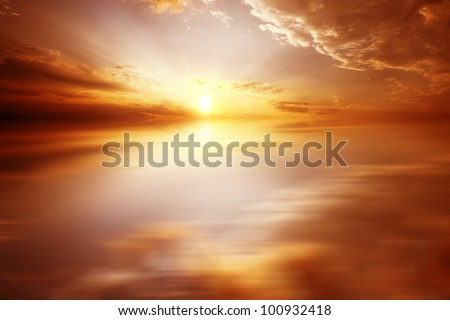 Red sunset over the sea, rich in dark clouds, rays of light