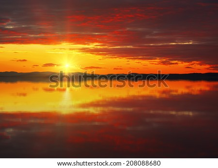 Red sunset sky with vivid dark clouds and rays of sunlight reflected in the water