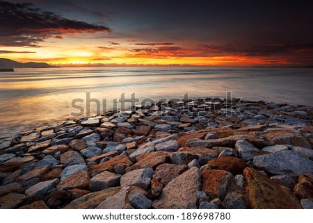 Red sunset with rocks - stock photo