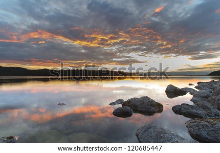 red sunsets reflected in the clear water of the lake Kronotskoye, Kamchatka, Russia
