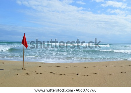 Red surf life saving flag in the sand with waves in the background and blue cloudy sky at Playa Cocles, Costa Rica