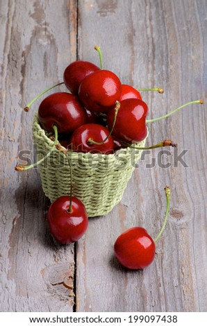 Red Sweet Cherries in Green Wicker Basket isolated on Rustic Wooden background - stock photo